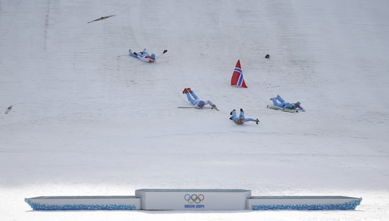 (From R) Norway's winning team members Haavard Klemetsen, Magnus Krog, Joergen Graabak and Magnus Hovdal Moan celebrate by sliding after the flower ceremony for the Nordic Combined team Gundersen event of the Sochi 2014 Winter Olympic Games, at the RusSki Gorki Ski Jumping Center in Rosa Khutor, February 20, 2014. (REUTERS/Kai Pfaffenbach)