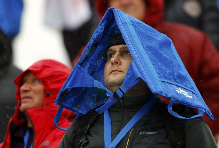 Spectator covers from rain as he watches the first run of the women's alpine skiing giant slalom event during the 2014 Sochi Winter Olympics at the Rosa Khutor Alpine Center February 18, 2014. (REUTERS/Kai Pfaffenbach)
