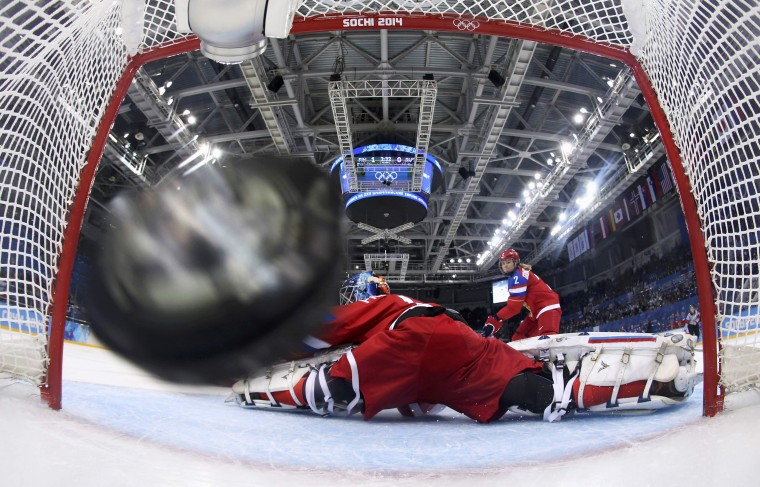 The puck flies into the net for Finland's second goal next to Russia's goalie Anna Prugova during the first period of their women's ice hockey classification game at the Sochi 2014 Winter Olympic Games February 18, 2014. (REUTERS/Martin Rose/Pool)