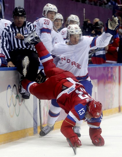 Norway's Alexander Bonsaksen upends Russia's Pavel Datsyuk (13), which resulted in a penalty for tripping, during the first period of their men's qualification round ice hockey game at the 2014 Sochi Winter Olympic Games, February 18, 2014. (REUTERS/Mark Blinch)