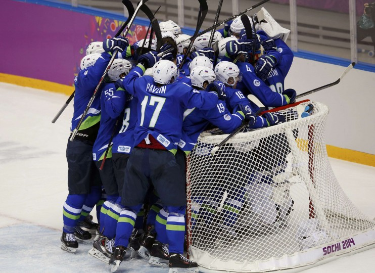 Slovenian players crowd near the goal to celebrate after defeating Austria in their men's ice hockey playoffs qualification game at the 2014 Sochi Winter Olympics February 18, 2014. (REUTERS/Grigory Dukor)
