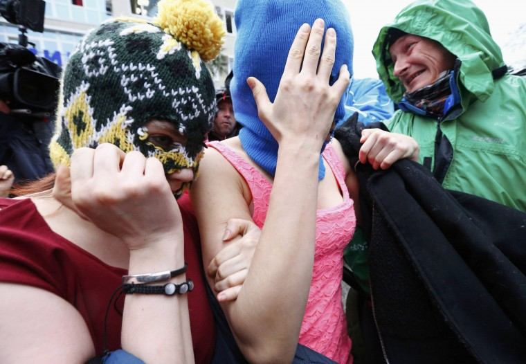 Masked members of Pussy Riot cover their faces as they leave a police station in Adler during the 2014 Sochi Winter Olympics, February 18, 2014. Pussy Riot protest band members Maria Alyokhina and Nadezhda Tolokonnikova were released from police custody on Tuesday, Tolokonnikova's husband said hours after they were detained in Sochi, where Russia is holding the 2014 Winter Olympics. (REUTERS/Shamil Zhumatov)