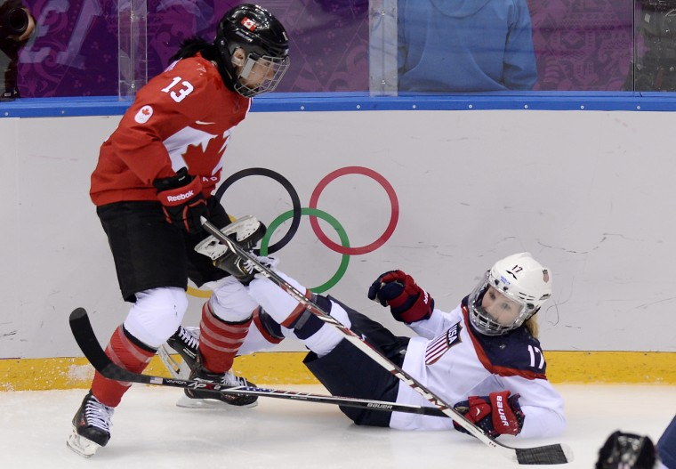 Canada's Caroline Ouellette (L) vies for the puck with US Jocelyne Lamoureux during the Women's Ice Hockey Gold Medal Game between Canada and USA at the Bolshoy Ice Dome during the Sochi Winter Olympics on February 20, 2014. (Alexander Nemenov/AFP/Getty Images)