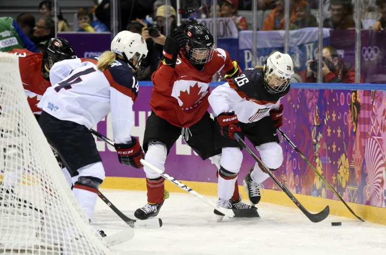 Canada defenseman Meaghan Mikkelson (12) reaches for the puck between USA forward Brianna Decker (14) and forward Kendall Coyne (26) in the women's ice hockey gold medal game during the Sochi 2014 Olympic Winter Games at Bolshoy Ice Dome. (Richard Mackson-USA TODAY Sports)
