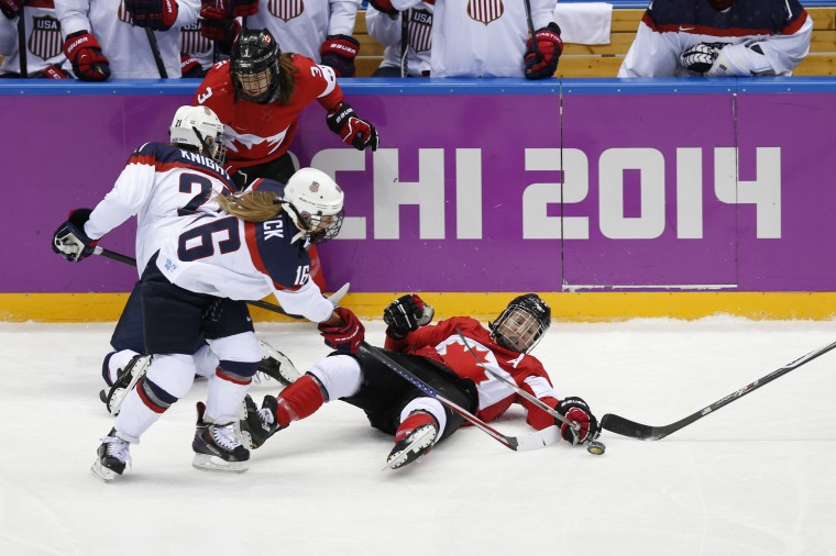 Canada forward Hayley Wickenheiser (22) and USA forward Kelli Stack (16) battle for the puck in the women's ice hockey gold medal game during the Sochi 2014 Olympic Winter Games at Bolshoy Ice Dome. (Winslow Townson-USA TODAY Sports)