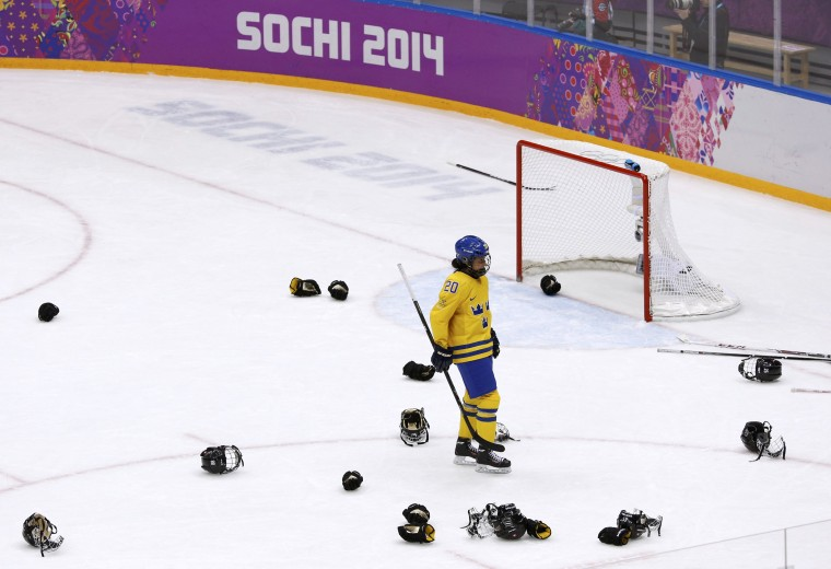 Sweden's Fanny Rask skates through the helmets and gloves of Switzerland's celebrating players at the end of their women's ice hockey bronze medal game at the Sochi 2014 Winter Olympic Games February 20, 2014. (REUTERS/Grigory Dukor)