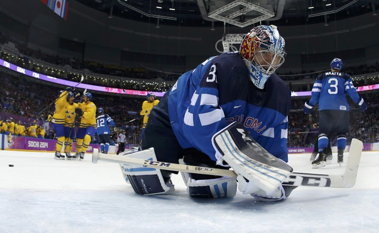 Finland's goalie Kari Lehtonen reacts as Sweden's Loui Eriksson celebrates with teammates after scoring a goal during the second period of their men's play-off semi-final ice hockey game at the Sochi 2014 Winter Olympic Games, February 21, 2014. (REUTERS/Julio Cortez)
