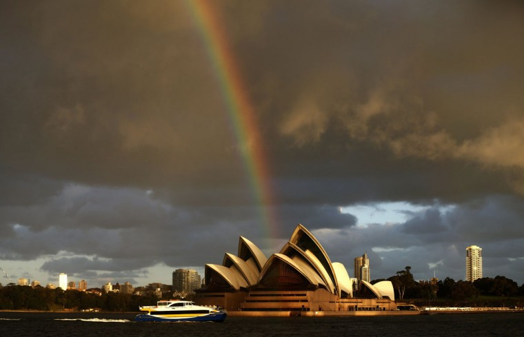 A passenger ferry navigates past the Sydney Opera House, as a rainbow is seen in the sky on a sunny winter afternoon July 31, 2013. (Daniel Munoz/Reuters)