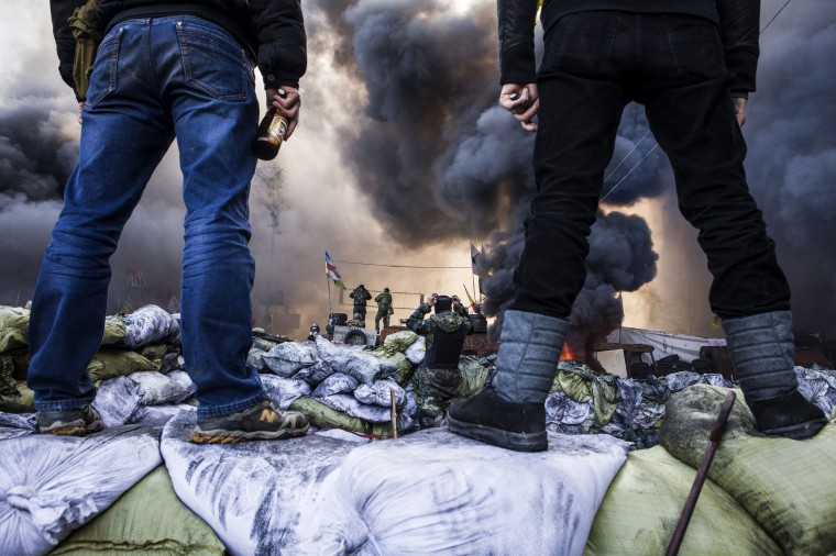 "Anti-government demonstrators stand on barricades during clashes with riot police in Kiev on February 18, 2014. Opposition leader Vitali Klitschko on February 18 urged women and children to leave the opposition's main protest camp on Kiev's Independence Square, known as Maidan, as riot police massed nearby. ""We ask women and children to quit Maidan as we cannot rule out the possibility that they will storm (the camp),"" the former heavyweight boxing champion told protestors on the square. (Sandro Maddalena/AFP/Getty Images)"