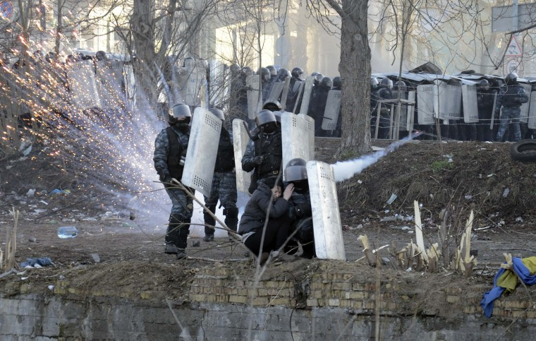 Riot police officers and a woman take cover behind shields during clashes between anti-government protesters with police in Kiev, February 18, 2014. Ukrainian riot police advanced on the heart of 12-week-old protests against President Viktor Yanukovich on Tuesday and security forces set a deadline to end disturbances after at least five protesters were reported killed in a day of clashes. (REUTERS/Maks Levin)