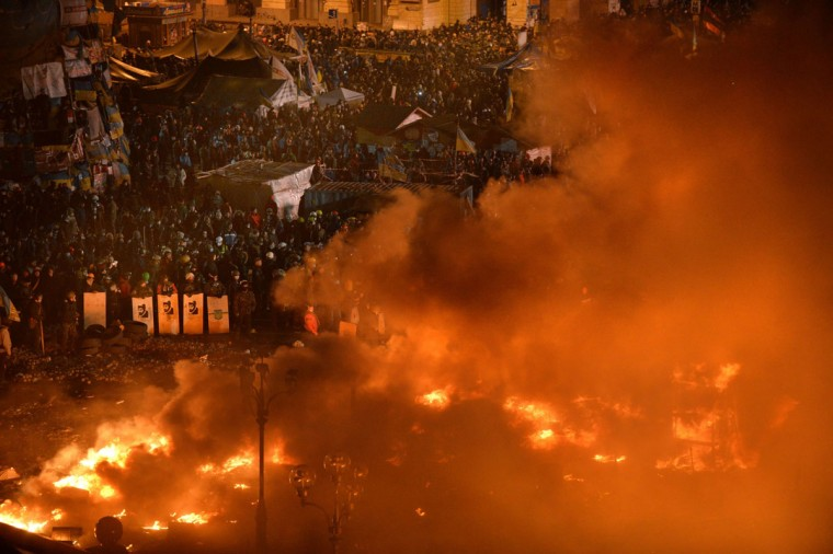Anti-government protesters clash with the police during their storming of Independence Square in Kiev on February 18, 2014. Flames engulfed the main anti-government protest camp on Kiev's Independence Square as riot police tried to force demonstrators out following the bloodiest clashes in three months of protests. The iconic square turned into a war zone as riot police moved slowly through opposition barricades from several directions, hurling stun grenades and using water cannon to clear protestors. (Sergei Supinsky/AFP/Getty Images)