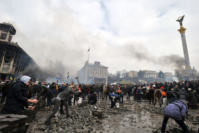 Anti-government protesters dig up cobblestones to use them as rocks against riot police on Kiev's Independence square on February 19, 2014. Protesters braced on February 19 for a fresh assault by riot police in central Kiev after a day of clashes left at least 25 people dead in the worst violence since the start of Ukraine's three-month political crisis. As dawn rose over Kiev's battered city centre, protesters hurled paving stones and Molotov cocktails at lines of riot police that had pushed into the heart of the devastated protest camp on Independence Square. (Genya Savilov/AFP/Getty Images)
