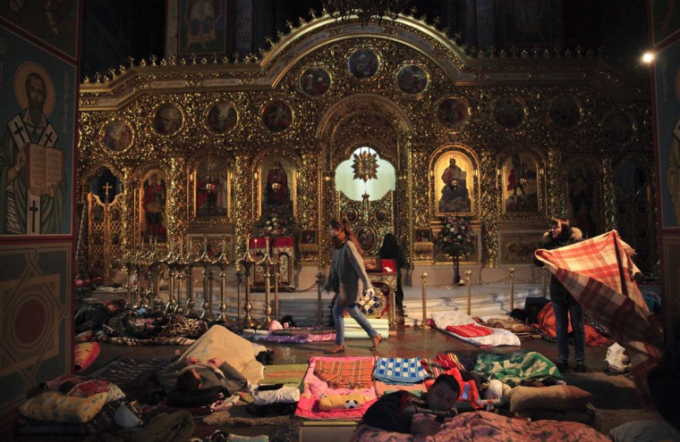 People rest inside Mikhailovsky Zlatoverkhy Cathedral (St. Michael's golden-domed cathedral), which serves as a temporary shelter and a first-aid post for anti-government protesters, in Kiev February 19, 2014. Ukrainian President Viktor Yanukovich accused pro-European opposition leaders on Wednesday of trying to seize power by force after at least 26 people died in the worst violence since the former Soviet republic gained independence. (REUTERS/David Mdzinarishvili)