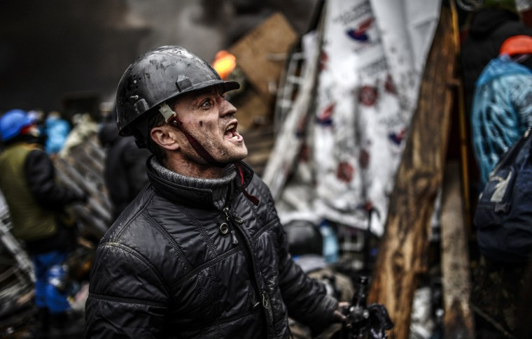 "A protester stands behind barricades during clashes with police on February 20, 2014 in Kiev. Ukraine's embattled leader announced a ""truce"" with the opposition as he prepared to get grilled by visiting EU diplomats over clashes that killed 26 and left the government facing diplomatic isolation. The shocking scale of the violence three months into the crisis brought expressions of grave concern from the West and condemnation of an ""attempted coup"" by the Kremlin. (Bulent Kilic/AFP/Getty Images)"