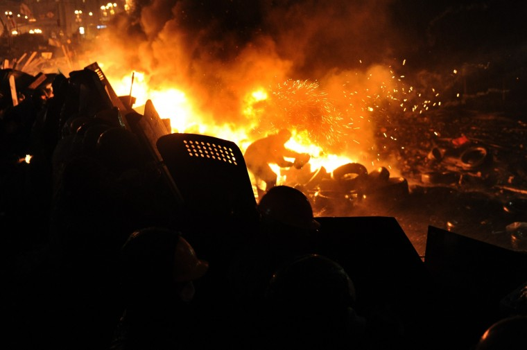 "A protester throws tyres to keep a barricade of flames between protesters and police at Independence square in Kiev on February 19, 2014. Ukrainian President Viktor Yanukovych on Wednesday announced a ""truce"" and the start of direct talks with the opposition after holding private talks with three anti-government leaders. (Louisa Gouliamaki/AFP/Getty Images)"