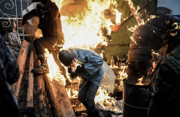 "Protesters burn as they stand behind burning barricades during clashes with police on February 20, 2014 in Kiev. Ukraine's embattled leader announced a ""truce"" with the opposition as he prepared to get grilled by visiting EU diplomats over clashes that killed 26 and left the government facing diplomatic isolation. The shocking scale of the violence three months into the crisis brought expressions of grave concern from the West and condemnation of an ""attempted coup"" by the Kremlin. (Bulent Kilic/AFP/Getty Images)"