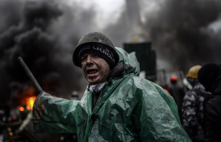 "A protester stands behind barricades during clashes with police on February 20, 2014 in Kiev. Ukraine's embattled leader announced a ""truce"" with the opposition as he prepared to get grilled by visiting EU diplomats over clashes that killed 26 and left the government facing diplomatic isolation. The shocking scale of the violence three months into the crisis brought expressions of grave concern from the West and condemnation of an ""attempted coup"" by the Kremlin. At least 25 protesters were killed on February 20 in fresh clashes between thousands of demonstrators and heavily-armed riot police in the heart of Kiev, AFP correspondents at the scene said. The bodies of eight demonstrators were lying outside Kiev's main post office on Independence Square, an AFP reporter said. The bodies of 17 other demonstrators with apparent gunshot wounds were also seen in the vicinity of two hotels on opposite sides of the protest encampment. (Bulent Kilic/AFP/Getty Images)"
