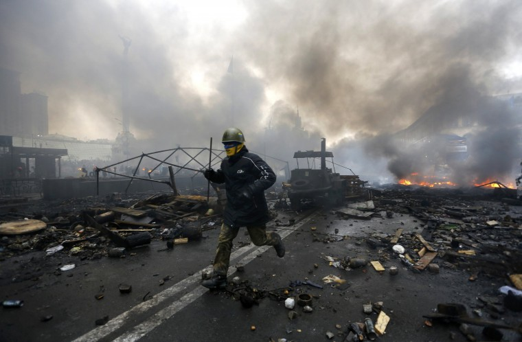 "An anti-government protester runs trough the rubble after violence erupted in the Independence Square in Kiev February 20, 2014. Ukrainian protesters hurling petrol bombs and paving stones drove riot police from the central square in Kiev on Thursday despite a ""truce"" which embattled Ukrainian President Viktor Yanukovich said he had agreed with opposition leaders. (REUTERS/Yannis Behrakis)"