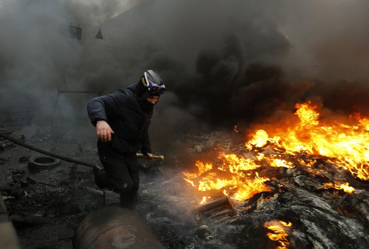 "An anti-government protester advances through a burning barricade in Kiev's Independence Square February 20, 2014. Ukrainian protesters hurling petrol bombs and paving stones drove riot police from the central square in Kiev on Thursday despite a ""truce"" which embattled Ukrainian President Viktor Yanukovich said he had agreed with opposition leaders. (REUTERS/Yannis Behrakis)"