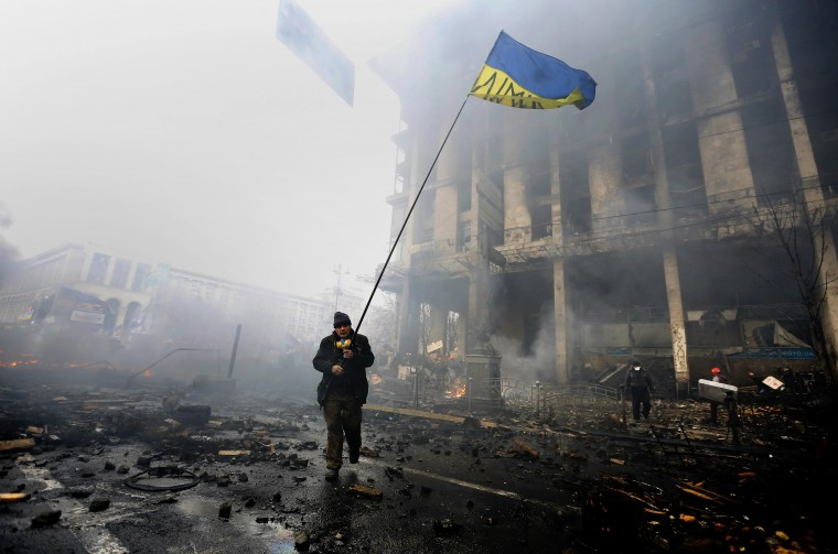 "An anti-government protester holds a Ukranian flag as he advances through burning barricades in Kiev's Independence Square February 20, 2014. Ukrainian protesters hurling petrol bombs and paving stones drove riot police from the central square in Kiev on Thursday despite a ""truce"" which embattled Ukrainian President Viktor Yanukovich said he had agreed with opposition leaders. (REUTERS/Yannis Behrakis)"