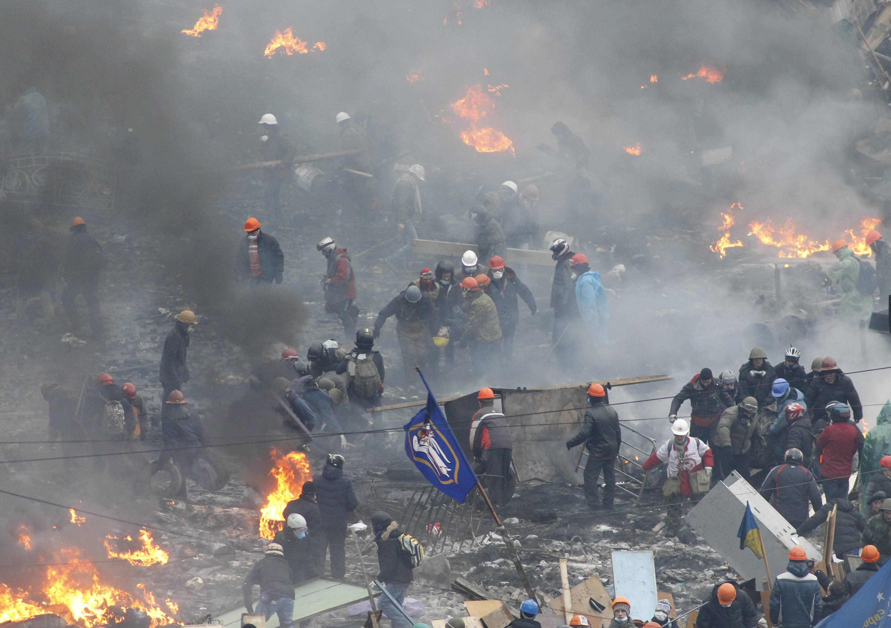 Anti-government protesters carry an injured man on a stretcher in    Ukraine Revolution Fire