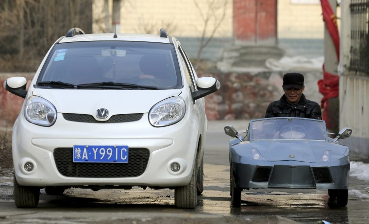 "Guo, a farmer in his 50s, drives his self-made scale replica of a Lamborghini past a car on a street in Zhengzhou, Henan province February 19, 2014. Guo spent 6 months and about 5,000 yuan (821 USD) to make the 2-metre-long, 1 metre-wide ""Lamborghini"" as a toy for his grandson. The replica, mainly made of scrapped metals and parts from electricity bicycles, bears five sets of batteries and can travel as far as 60 km (37 miles) when fully charged, local media reported. Picture taken February 19, 2014. (REUTERS/China Daily)"