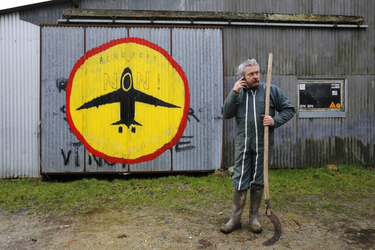 "French farmer Sylvain Fresneau makes a phone call as he stands in front of his farm at ""La Vacherie"" area in Notre-Dame-des-Landes, western France, February 14, 2014. Around two hundred people, farmers and inhabitants who refuse to leave, occupy houses or expropriated land in the zoned ZAD (Deferred Development Zone) in Notre-Dame-des-Landes, that is slated for the Grand Ouest Airport (AGO). The residents of the ZAD, 1,600 hectares (3,954 acres), have formed some fifty living groups comprised of self-built homes, villages, farms and buildings that were saved from destruction, which have been renovated and are currently occupied by people who resist expulsion. Residents work in agricultural and horticultural projects, and also have collective spaces for baking bread, a pharmacy, sewing and bicycle repair. A demonstration to protest the construction of the new airport in this zone, some 30kms (19 miles) from Nantes and scheduled for 2017, will be held February 22, 2014 in Nantes. Picture taken February 14, 2014. (REUTERS/Stephane Mahe)"