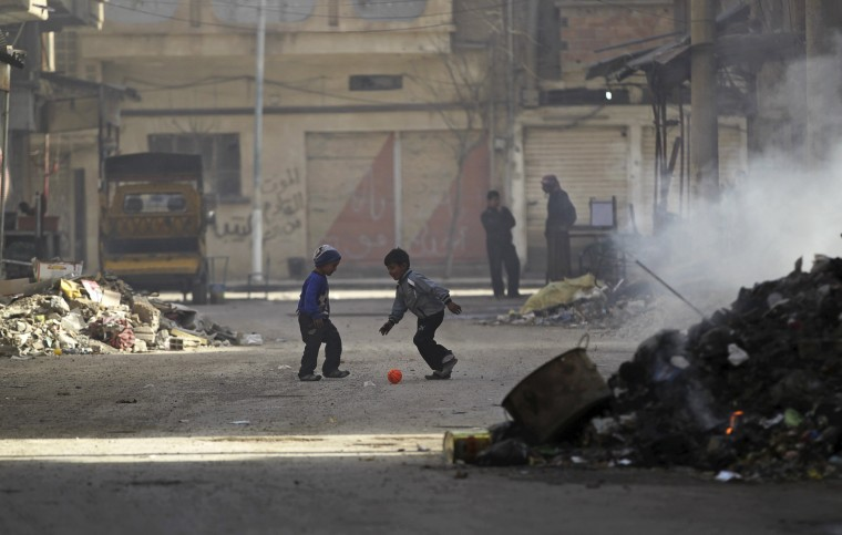 Boys play soccer next to a burning pile of garbage along a street filled with debris in Deir al-Zor, eastern Syria February 19, 2014. Picture taken February 19, 2014. (REUTERS/Khalil Ashawi)