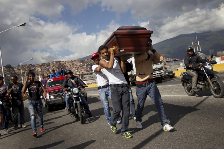 Relatives of a crime victim carry his coffin on a highway, as a tribute, prior to the victim's burial in Caracas November 27, 2012. A perpetually edgy city, Caracas' murder rate has shot up in recent years to become one of the world's worst. Both Venezuela's official national rate of 39 deaths a year per 100,000 people and an NGO tally of double that make the country an international leader in homicides, vying with gang-plagued nations such as Honduras and El Salvador. Some 100 undertakers' businesses, legal and illegal, have sprung up around Caracas in recent years. Nor is there a lack of demand for tomb-chisellers, flower-sellers, permit-handlers and a plethora of other mini-businesses purveying to death. Picture taken November 27, 2012. (REUTERS/Carlos Garcia Rawlins)