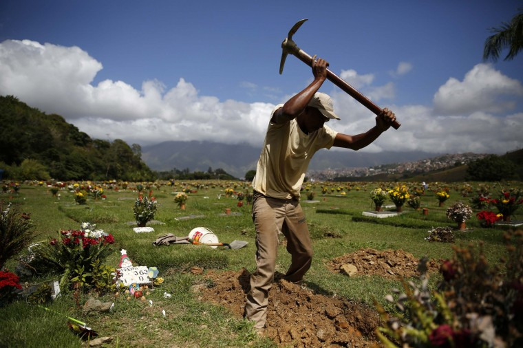 A worker digs a grave in the East Cemetery in Caracas December 27, 2013. A perpetually edgy city, Caracas' murder rate has shot up in recent years to become one of the world's worst. Both Venezuela's official national rate of 39 deaths a year per 100,000 people and an NGO tally of double that make the country an international leader in homicides, vying with gang-plagued nations such as Honduras and El Salvador. Some 100 undertakers' businesses, legal and illegal, have sprung up around Caracas in recent years. Nor is there a lack of demand for tomb-chisellers, flower-sellers, permit-handlers and a plethora of other mini-businesses purveying to death. Picture taken December 27, 2013. (REUTERS/Carlos Garcia Rawlins)