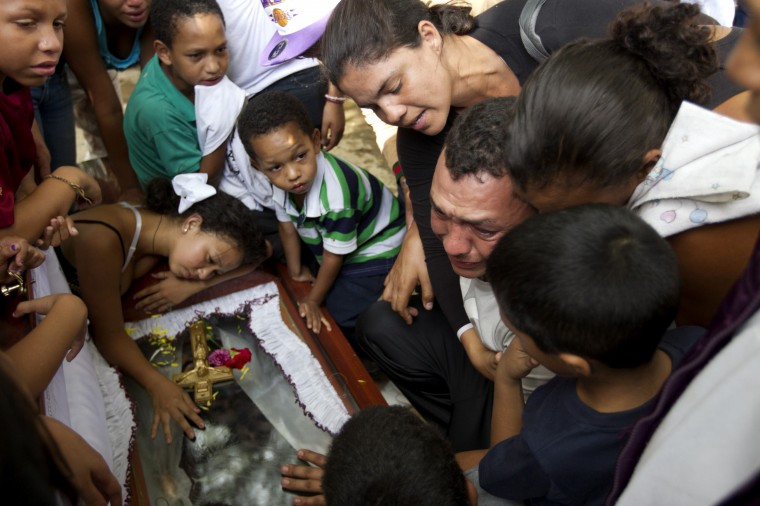 Relatives of a gunshot victim cry over his coffin during his funeral ceremony in Caracas November 27, 2012. A perpetually edgy city, Caracas' murder rate has shot up in recent years to become one of the world's worst. Both Venezuela's official national rate of 39 deaths a year per 100,000 people and an NGO tally of double that make the country an international leader in homicides, vying with gang-plagued nations such as Honduras and El Salvador. Some 100 undertakers' businesses, legal and illegal, have sprung up around Caracas in recent years. Nor is there a lack of demand for tomb-chisellers, flower-sellers, permit-handlers and a plethora of other mini-businesses purveying to death. Picture taken November 27, 2012. (REUTERS/Carlos Garcia Rawlins)
