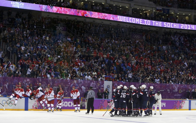 Team USA's T.J. Oshie and his teammates celebrate after he scored the game-winning shootout goal against Russia's goalie Sergei Bobrovski during their men's preliminary round ice hockey game at the 2014 Sochi Winter Olympics, February 15, 2014. REUTERS/Gary Hershorn
