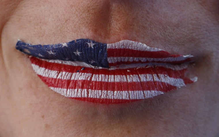 A fan of the U.S. is seen with lips painted in the colours of their national flag at the men's skeleton event during the 2014 Sochi Winter Olympics February 15, 2014. REUTERS/Arnd Wiegmann