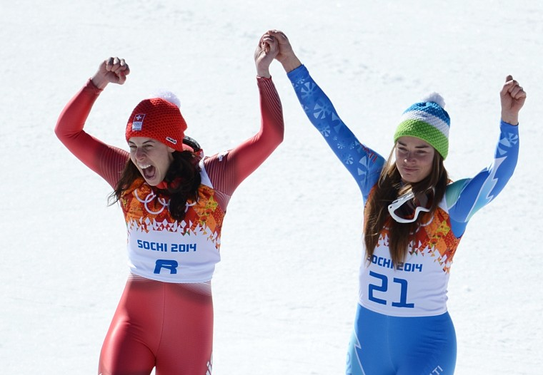 Gold medallists Slovenia's Tina Maze (R) and Switzerland's Dominique Gisin stand on the podium at the Women's Alpine Skiing Downhill Flower Ceremony at the Rosa Khutor Alpine Center during the Sochi Winter Olympics on February 12, 2014. (Krill Kudryavtse/AFP/Getty Images)