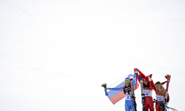 Joint winners Switzerland's Dominique Gisin (C) and Slovenia's Tina Maze pose with third-placed Switzerland's Lara Gut (R) at the flower ceremony after the women's alpine skiing downhill race at the 2014 Sochi Winter Olympics February 12, 2014. (REUTERS/Kai Pfaffenbach)