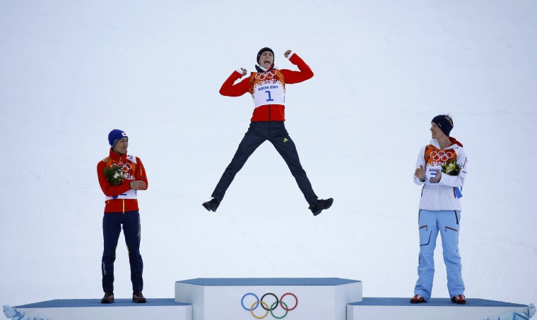 Winner Germany's Eric Frenzel (C) jumps on the podium as second-placed Japan's Akito Watabe (L) and third-placed Norway's Magnus Krog (R), applaud, during the flower ceremony for the Nordic Combined individual normal hill 10 km event of the Sochi 2014 Winter Olympic Games, at the RusSki Gorki Ski Jumping Center in Rosa Khutor, February 12, 2014. (REUTERS/Kai Pfaffenbach)