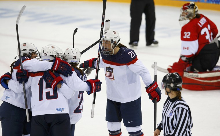Team USA's Hilary Knight (21) celebrates with her teammates after scoring on Canada's goalie Charline Labonte (R) during the second period of their women's ice hockey game at the 2014 Sochi Winter Olympics, February 12, 2014. (REUTERS/Brian Snyder)