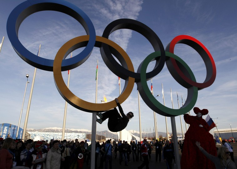 A woman hangs from a set of Olympic rings as she has her picture taken at the Olympic Park during the 2014 Sochi Winter Olympics February 12, 2014. (REUTERS/Gary Hershorn)