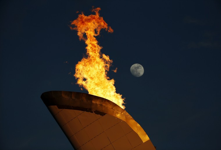 The Olympic flame burns in the cauldron as the moon rises over the Olympic Park during the 2014 Sochi Winter Olympics, February 12, 2014. (REUTERS/Eric Gaillard)