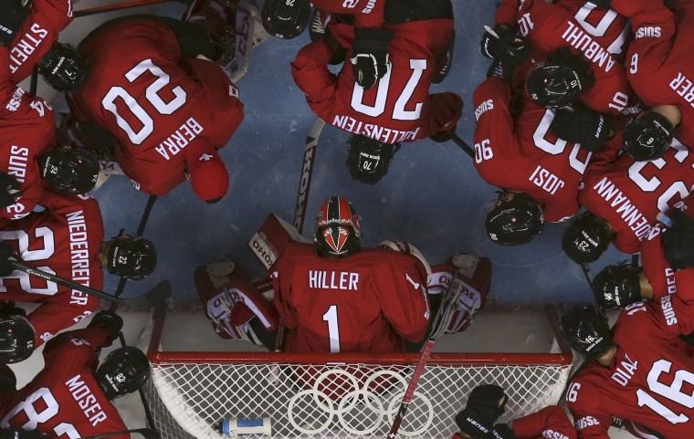 Teammates surround Switzerland's goalie Jonas Hiller before the start of their men's preliminary round hockey game against Latvia at the Sochi 2014 Winter Olympic Games February 12, 2014. REUTERS/Jim Young