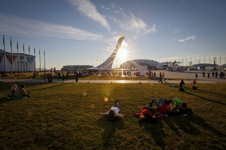 Fans enjoy a sunny day in front of the Olympic Cauldron and flame in the Olympic Park during the 2014 Winter Olympic Games in Sochi February 12, 2014. REUTERS/Shamil Zhumatov