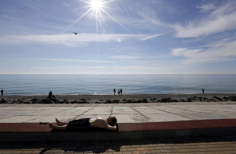 A man sun-bathes along the Black Sea near the Olympic Park during the 2014 Sochi Winter Olympics, February 12, 2014 . REUTERS/Reinhard Krause