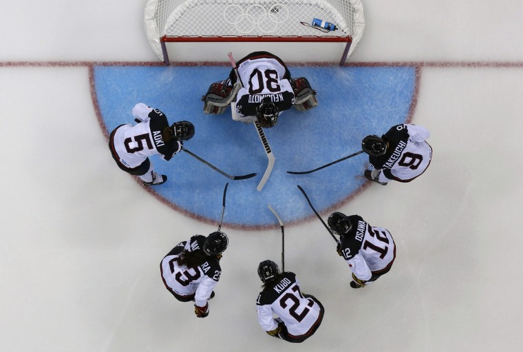 Members of Japan's women's ice hockey team surround Japan's goalie Nana Fujimoto before the start of the second period against Germany during their women's preliminary round ice hockey game at the Sochi 2014 Winter Olympic Games February 13, 2014. REUTERS/Laszlo Balogh