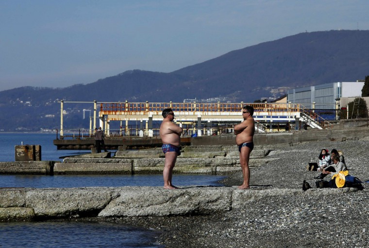 Two men sunbathe on the beach in Adler on a warm and sunny day during the 2014 Sochi Winter Olympics, February 13, 2014 REUTERS/Eric Gaillard