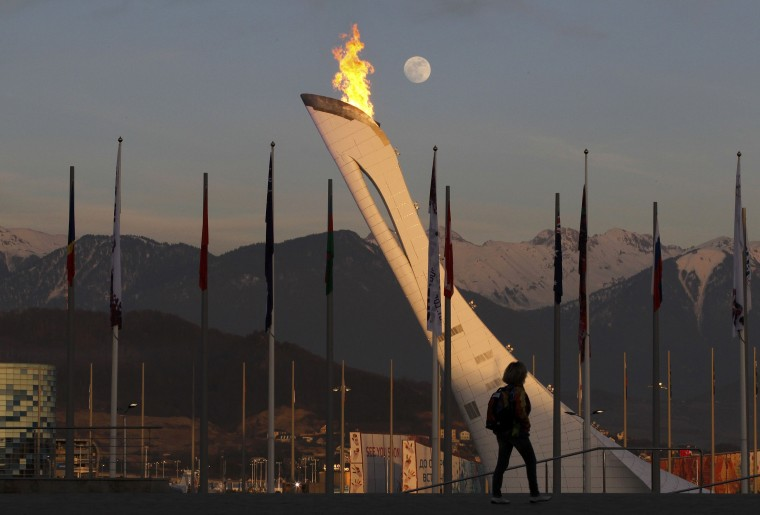 A woman walks past the cauldron at the Olympic Park as the moon rises over the Caucasus Mountains at the 2014 Sochi Winter Olympics, February 13, 2014. REUTERS/Gary Hershorn