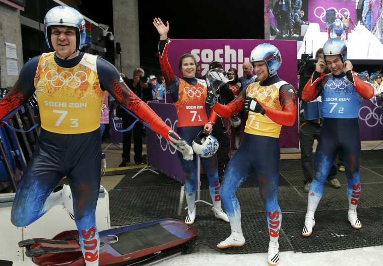 Russia's pilot Alexander Denisyev (L) celebrates with teammates Tatyana Ivanova (2nd L), Valdislav Antonov (3rd L) and Albert Demchenko during the luge team relay competition at the 2014 Sochi Winter Olympics at the Sanki Sliding Center February 13, 2014. REUTERS/Fabrizio Bensch