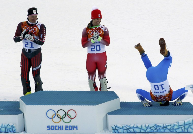 Third-placed Italy's Christof Innerhofer (R) does a somersault on the podium as winner Switzerland's Sandro Viletta (C) and second-placed Croatia's Ivica Kostelic laugh after the men's alpine skiing super combined event at the 2014 Sochi Winter Olympics at the Rosa Khutor Alpine Center February 14, 2014. REUTERS/Stefano Rellandini