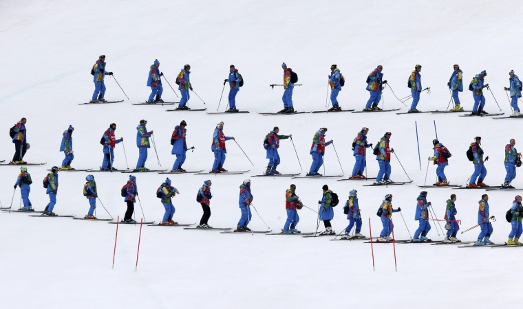Course slippers prepare the slalom piste ahead of the slalom run of the men's alpine skiing super combined event during the 2014 Sochi Winter Olympics at the Rosa Khutor Alpine Center in Rosa Khutor February 14, 2014. REUTERS/Mike Segar