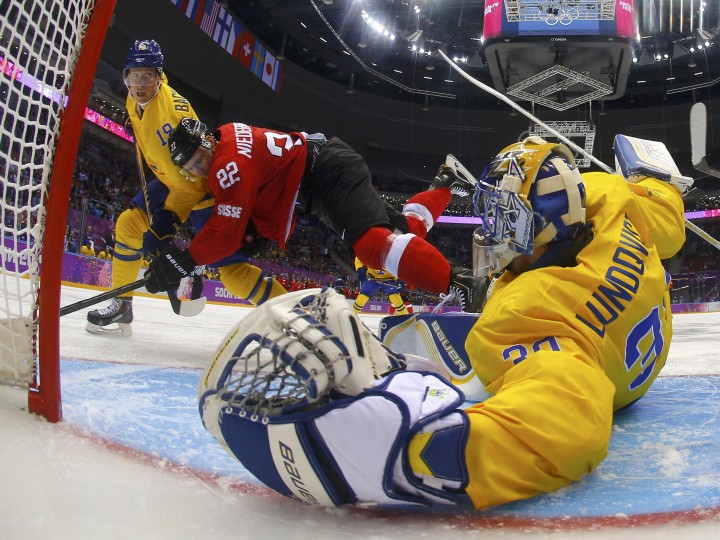 Sweden's goalie Henrik Lundqvist (R) makes a save on Switzerland's Nino Niederreiter as Sweden's Nicklas Backstrom defends during the first period of their men's preliminary round hockey game at the 2014 Sochi Winter Olympic Games, February 14, 2014. REUTERS/Mark Blinch/Pool