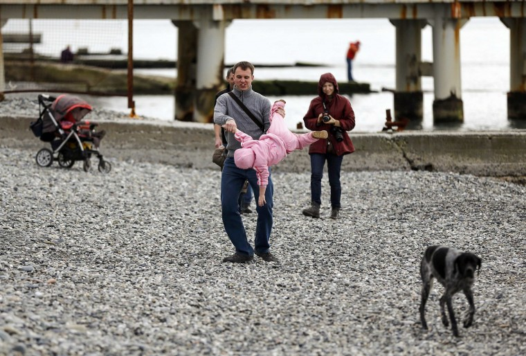 A man plays with his child on the beach in Adler on a warm and sunny day during the 2014 Sochi Winter Olympics February 14, 2014. REUTERS/Shamil Zhumatov